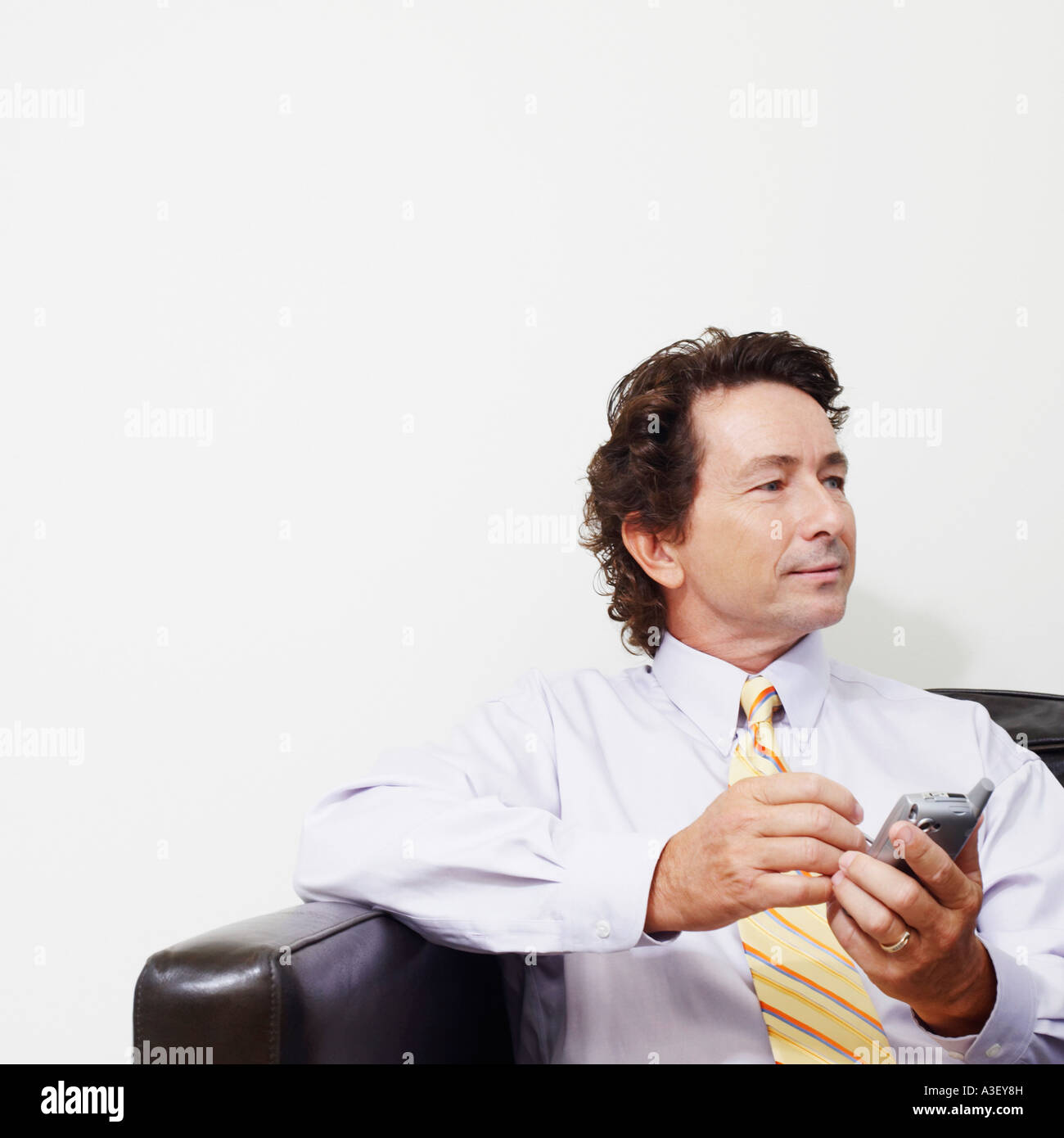 Businessman sitting on a couch and holding a mobile phone - Stock Image