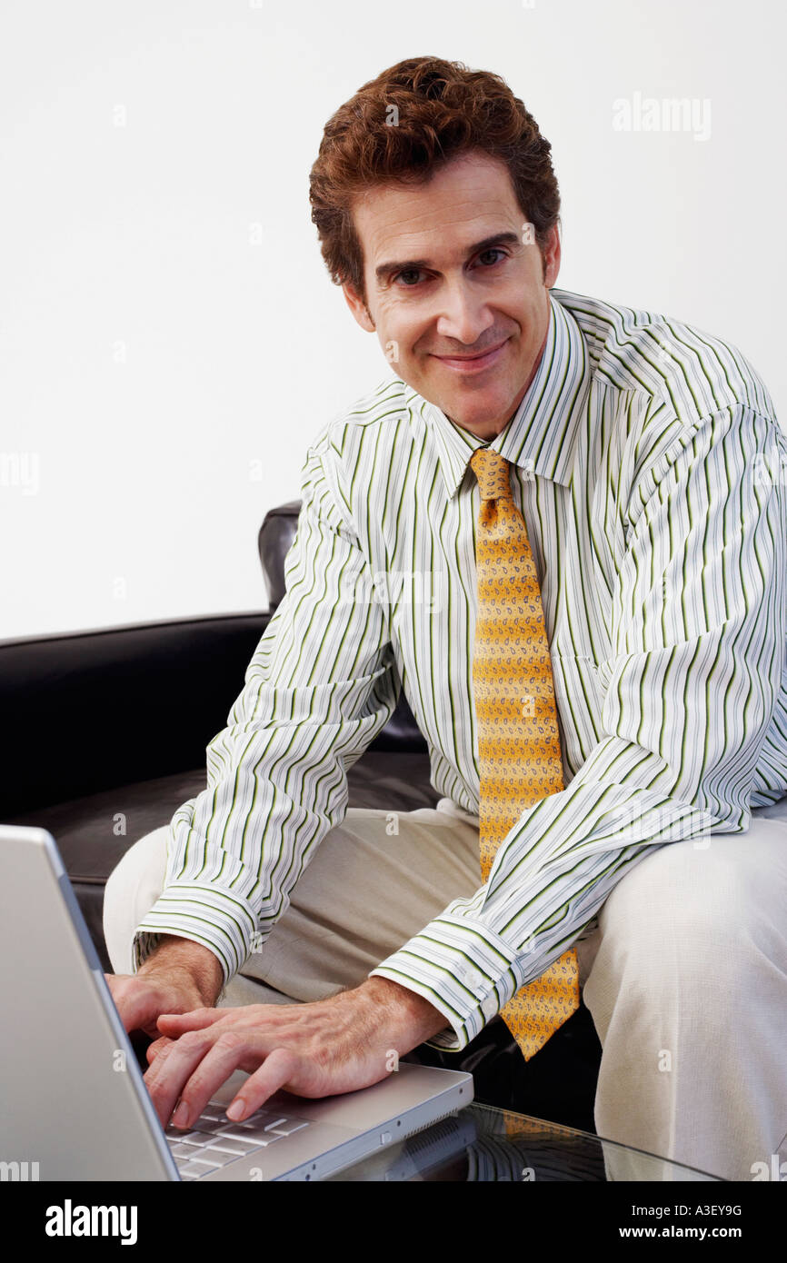 Portrait of a businessman sitting on a couch and using a laptop - Stock Image