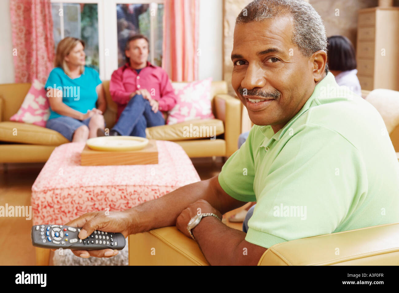 Portrait of a mature man operating a remote control with three mature people sitting beside him - Stock Image