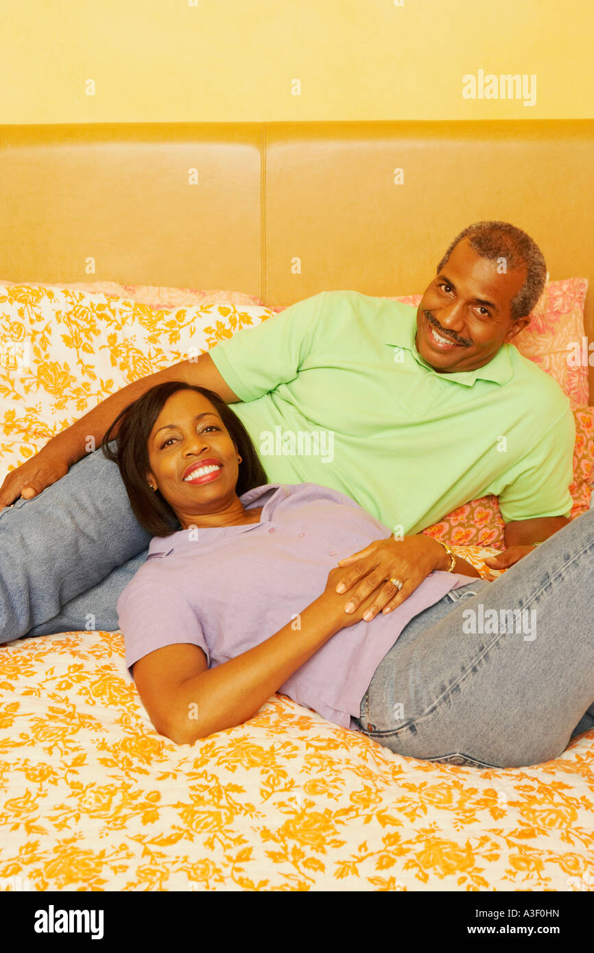 Portrait of a mature couple lying on the bed and smiling - Stock Image