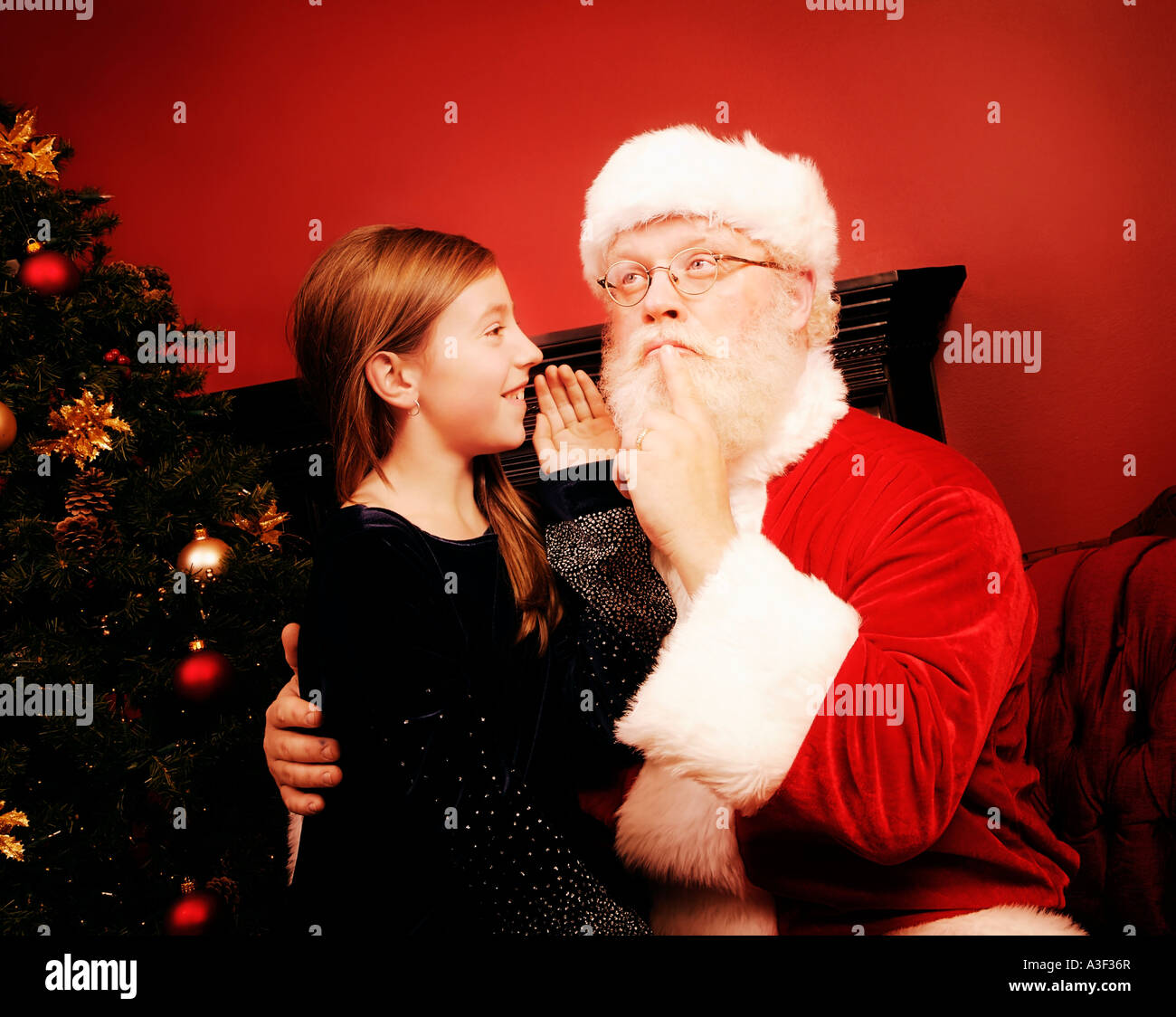 Young girl talking to Santa Claus - Stock Image