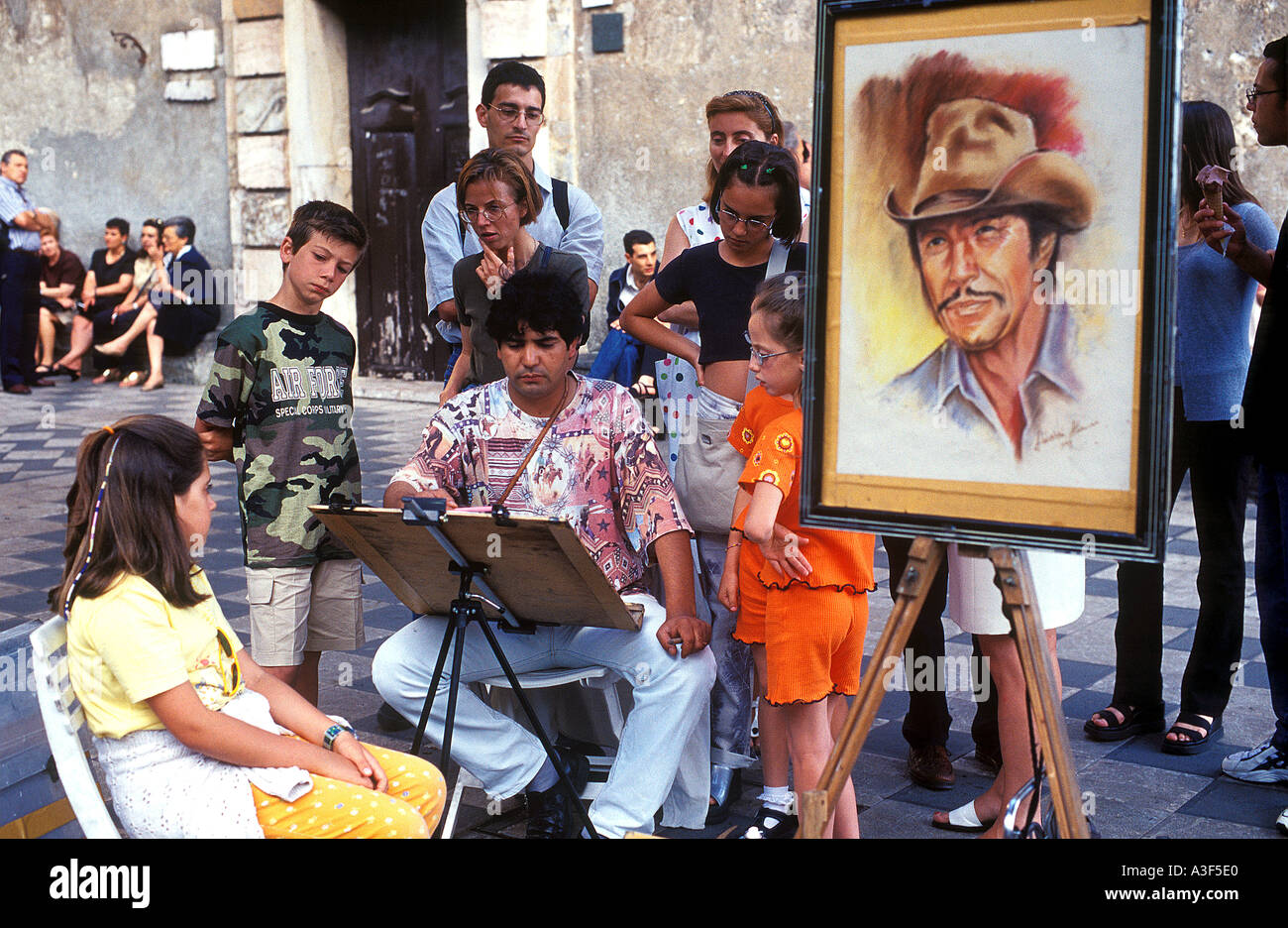 Street Artist painting passers-by in Taormina, Sicily, Italy - Stock Image