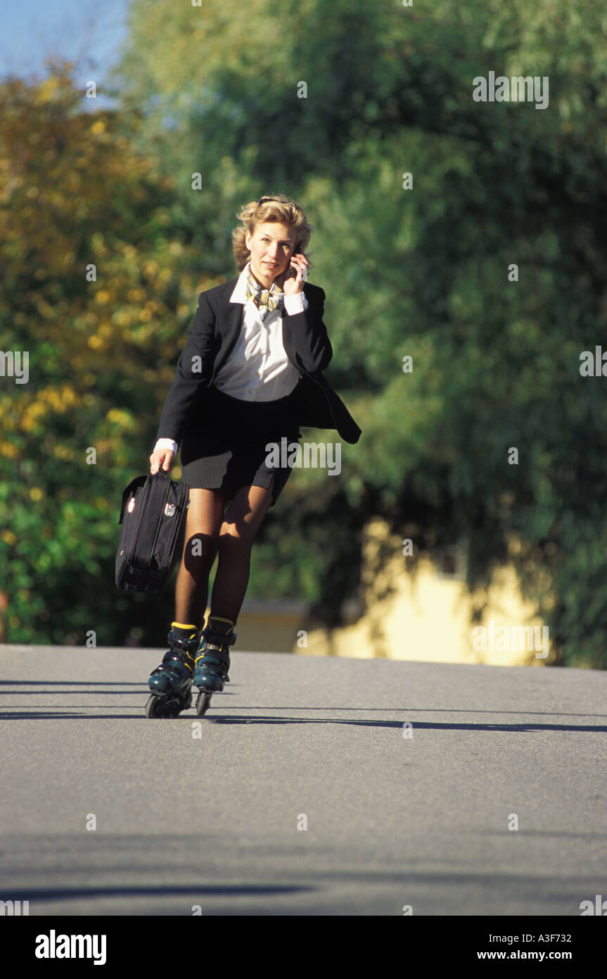 Woman on roller blades holding briefcase and talking on cellphone skating to work - Stock Image