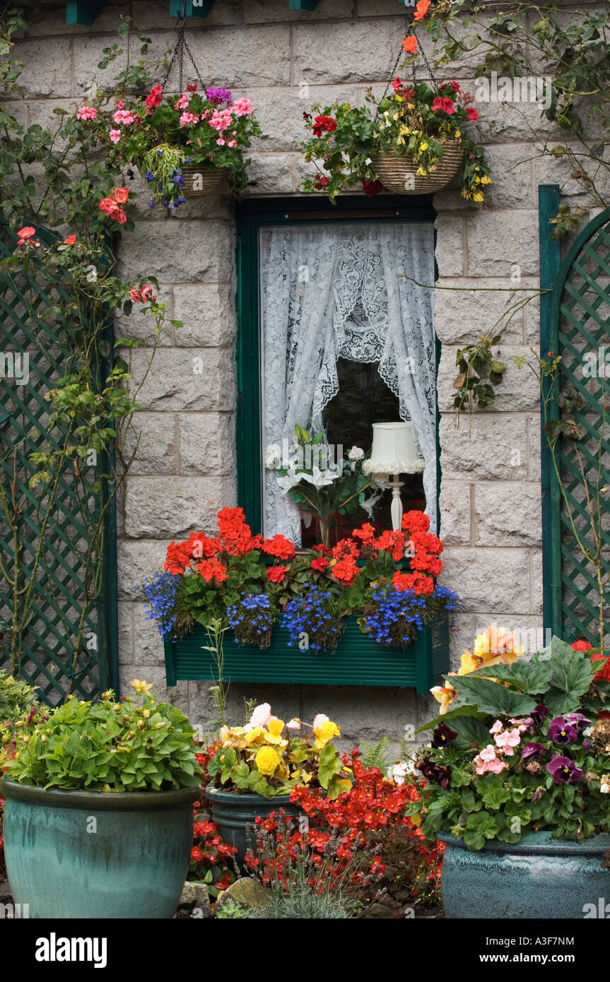 Flowers in Hanging Baskets Window Box Large Pots and Trellis Surrounding Window in Small Stone Cottage Glencoe Village Stock Photo
