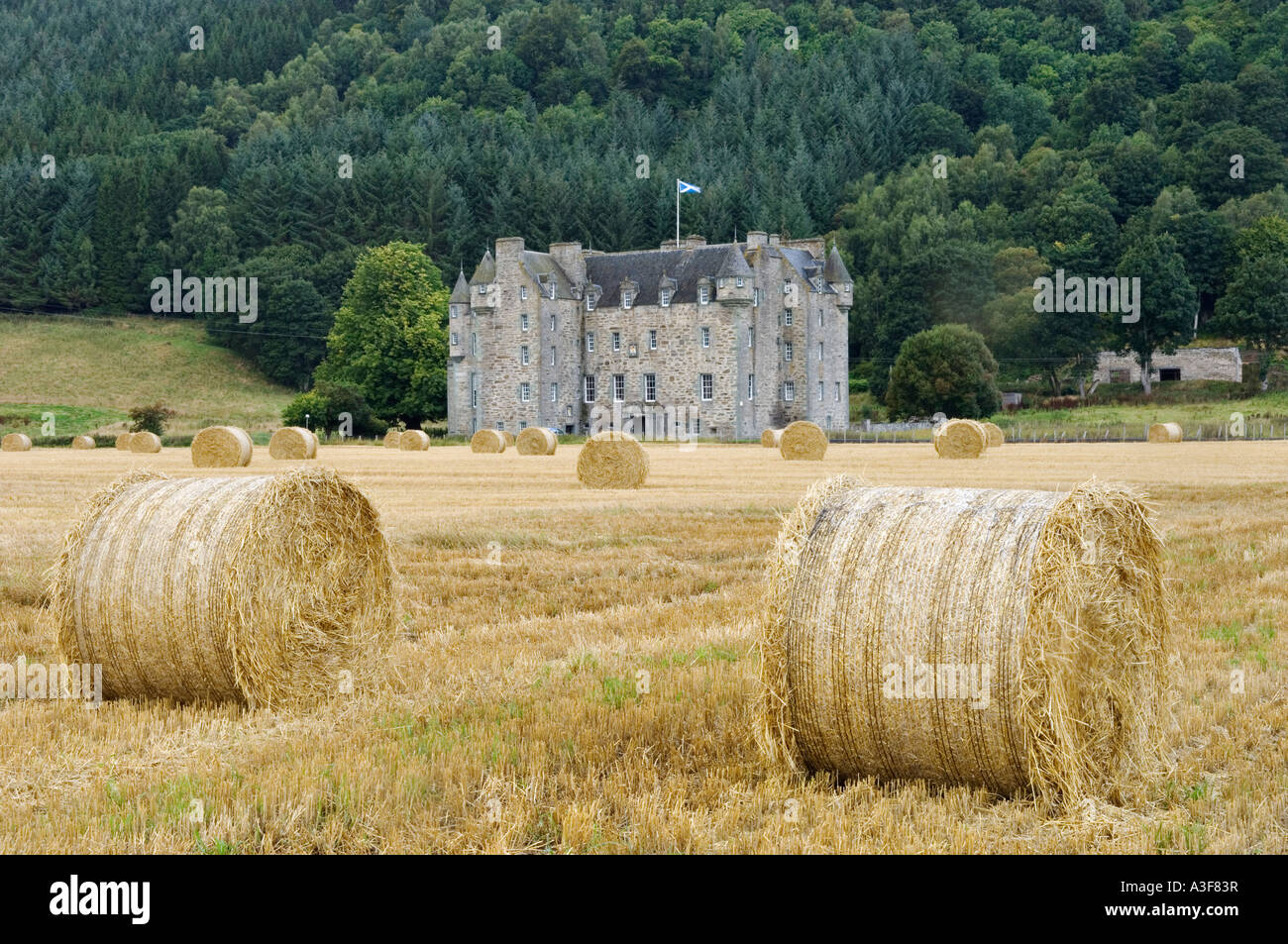 Castle Menzies Stands Amid Farm Field and Bales of Hay Near Weem Scotland - Stock Image