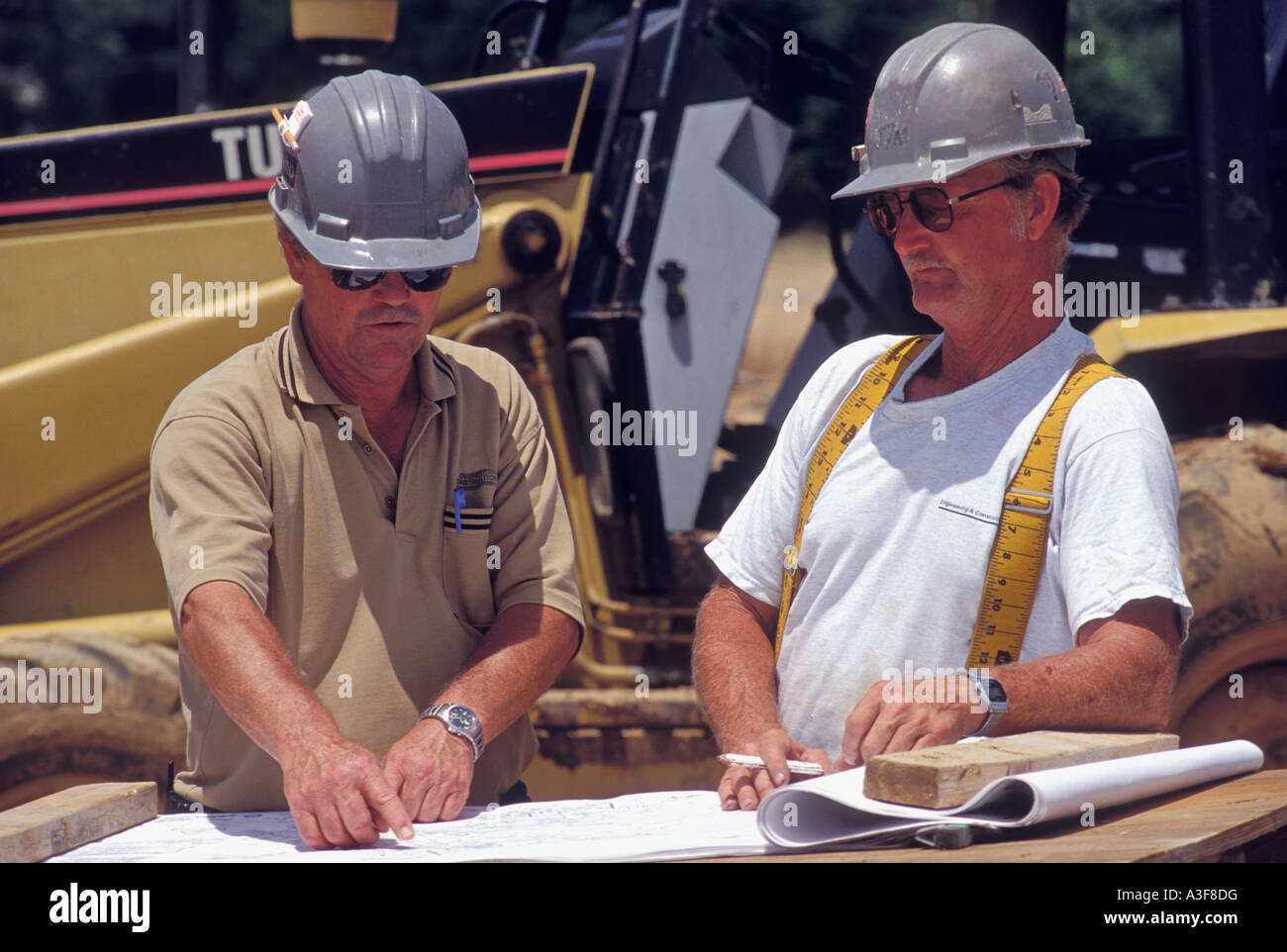 Engineer Pointing Out Detail on Blueprint To Construction Supervisor at Job Site United States - Stock Image