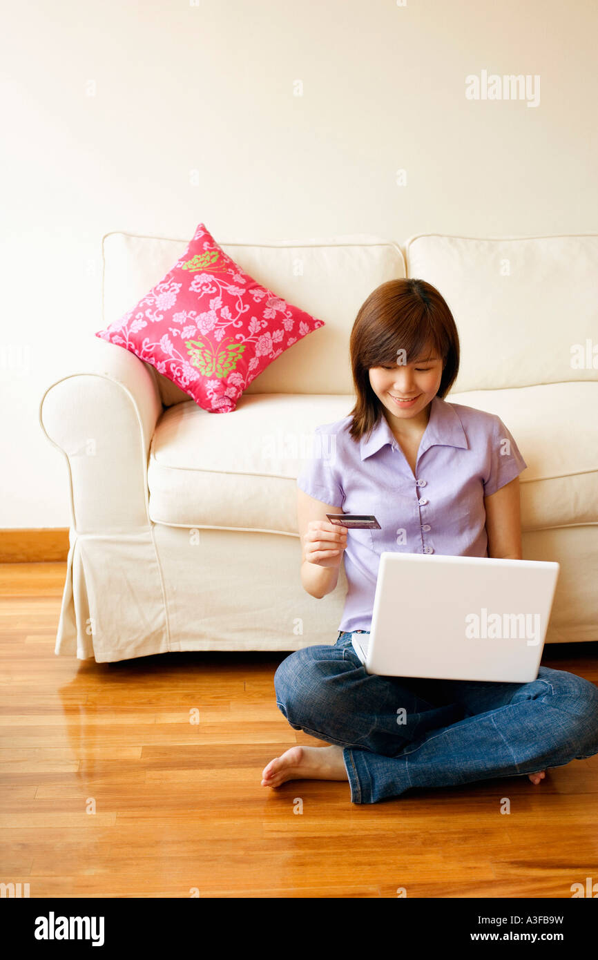 Young woman shopping online with a credit card - Stock Image