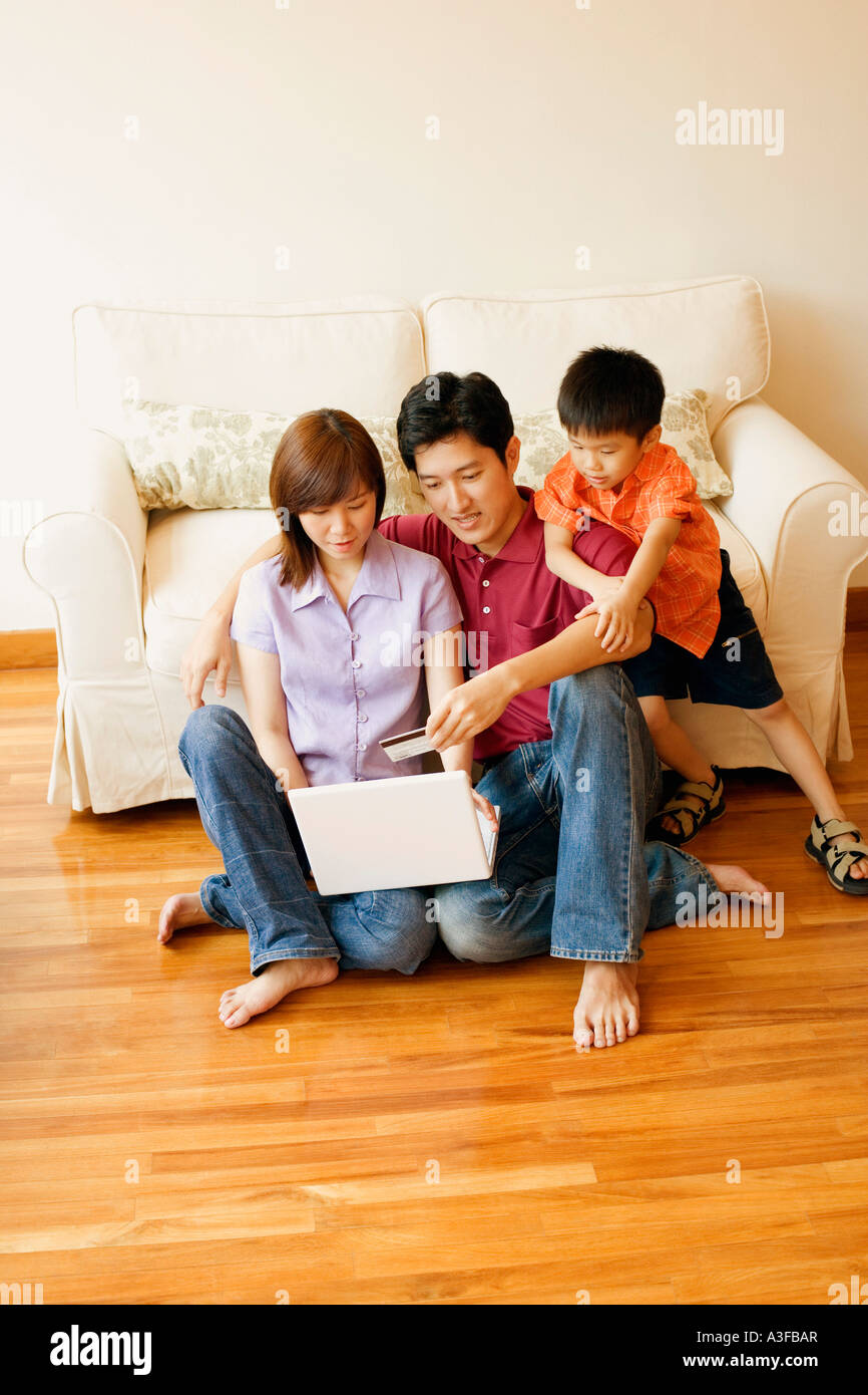 Young couple shopping online with a credit card and their son beside them - Stock Image