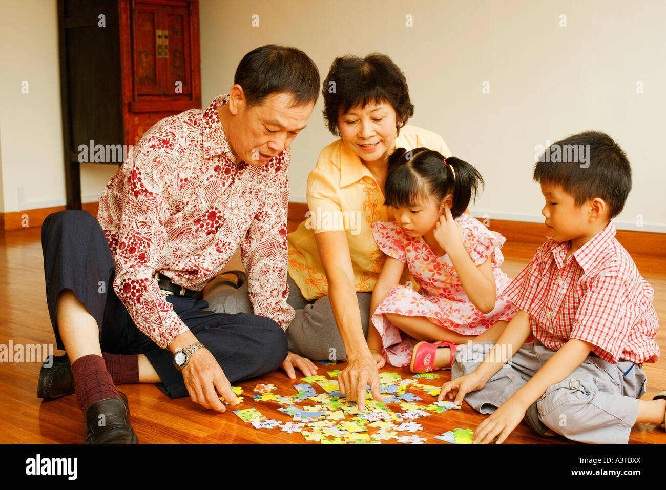 Boy with a girl and their grandparents playing with a jigsaw puzzle - Stock Image