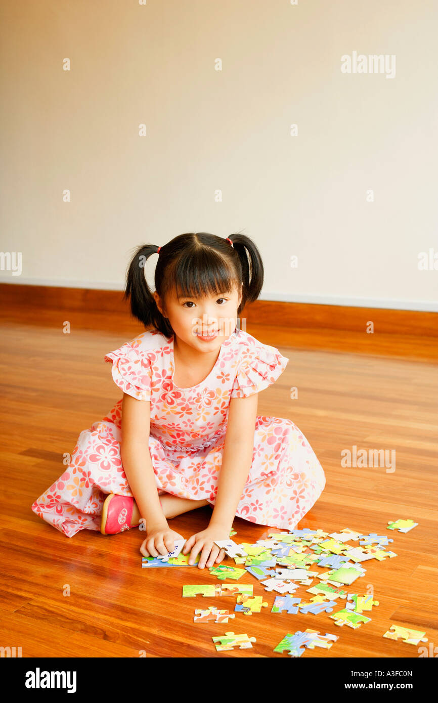 Portrait of a girl smiling and playing with a jigsaw puzzle - Stock Image