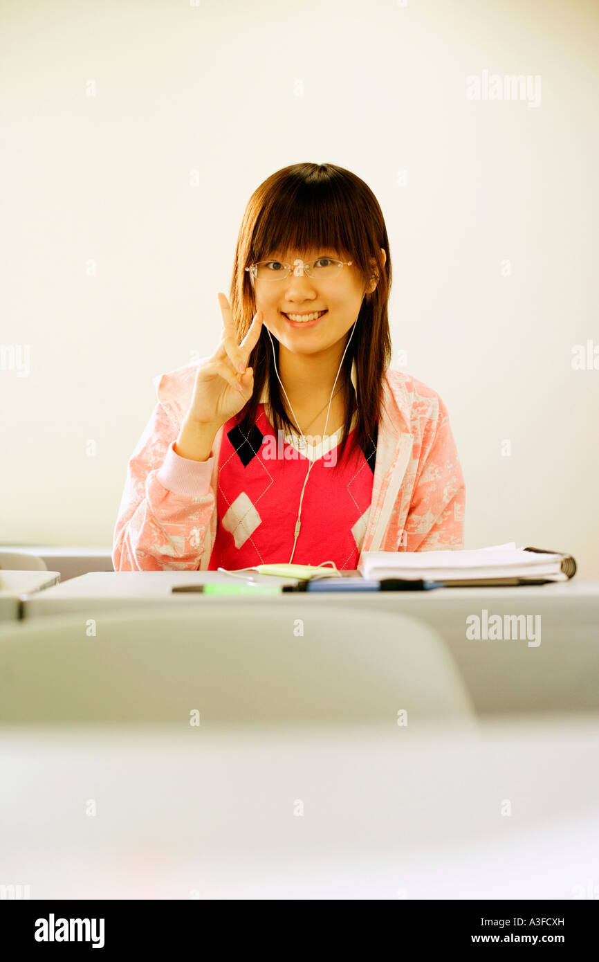 Portrait of a teenage girl making a peace sign in the classroom - Stock Image