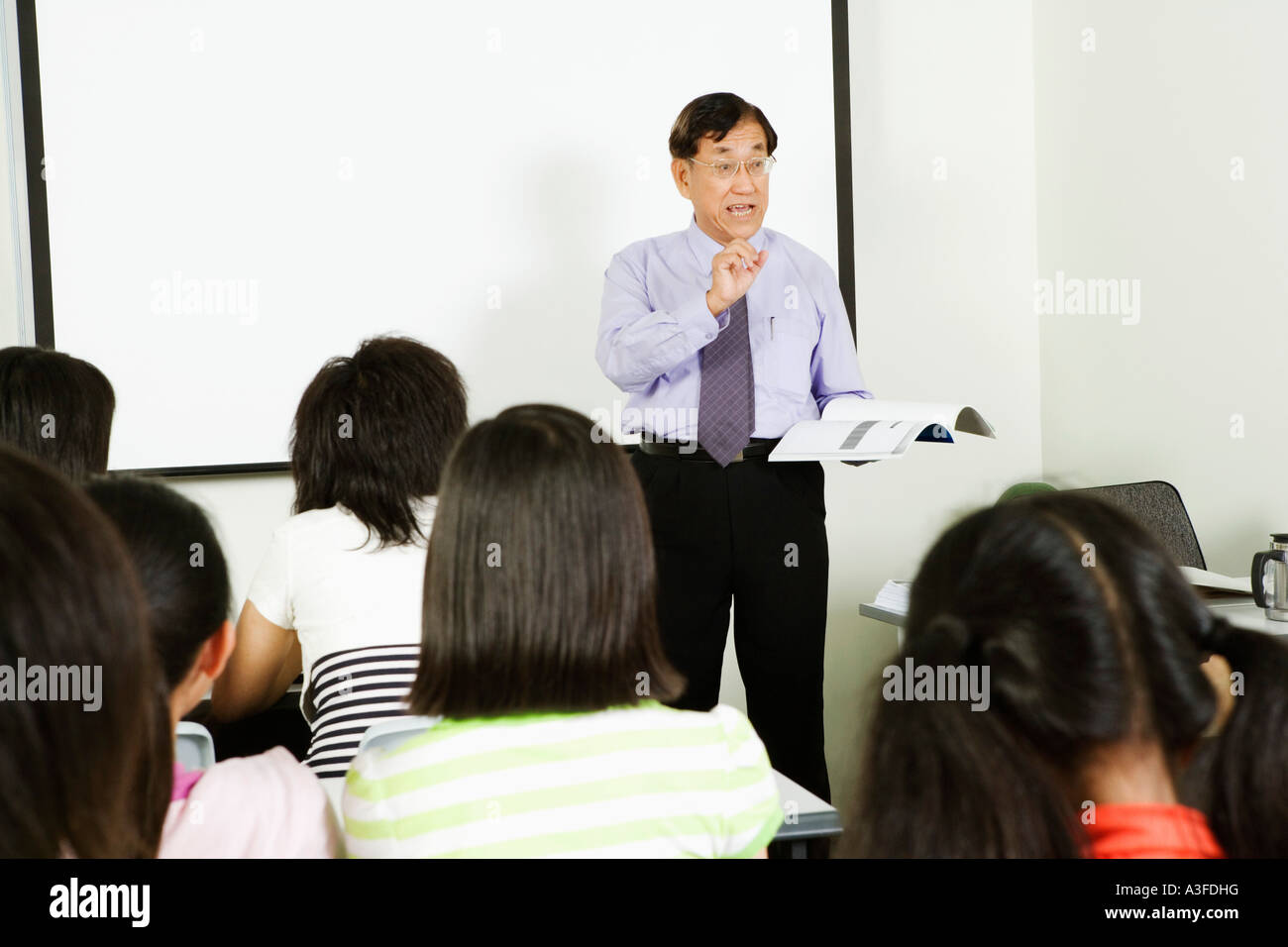 Teacher teaching in a classroom - Stock Image