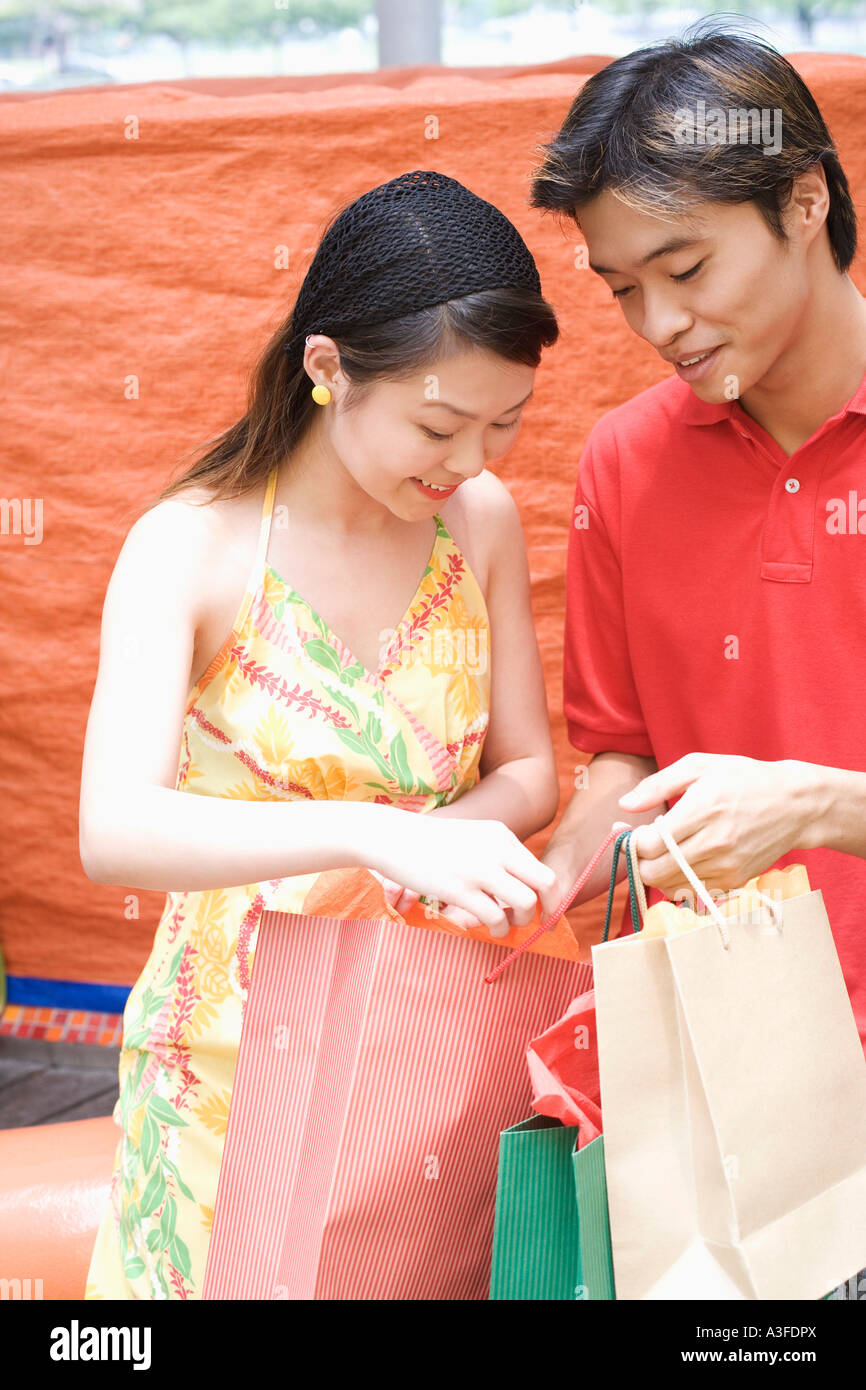 Close-up of a young couple looking into a shopping bag - Stock Image