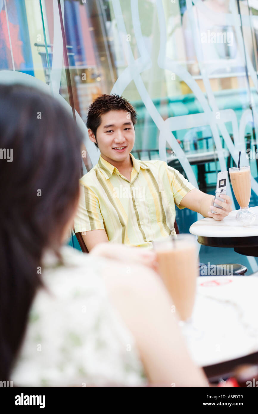 Young man sitting in a cafeteria and looking at mobile phone - Stock Image
