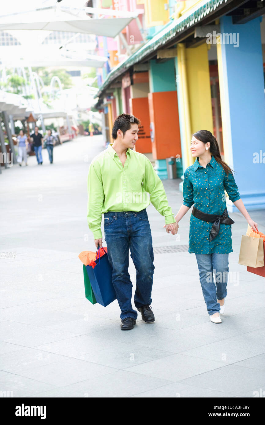 Young couple walking with shopping bags - Stock Image