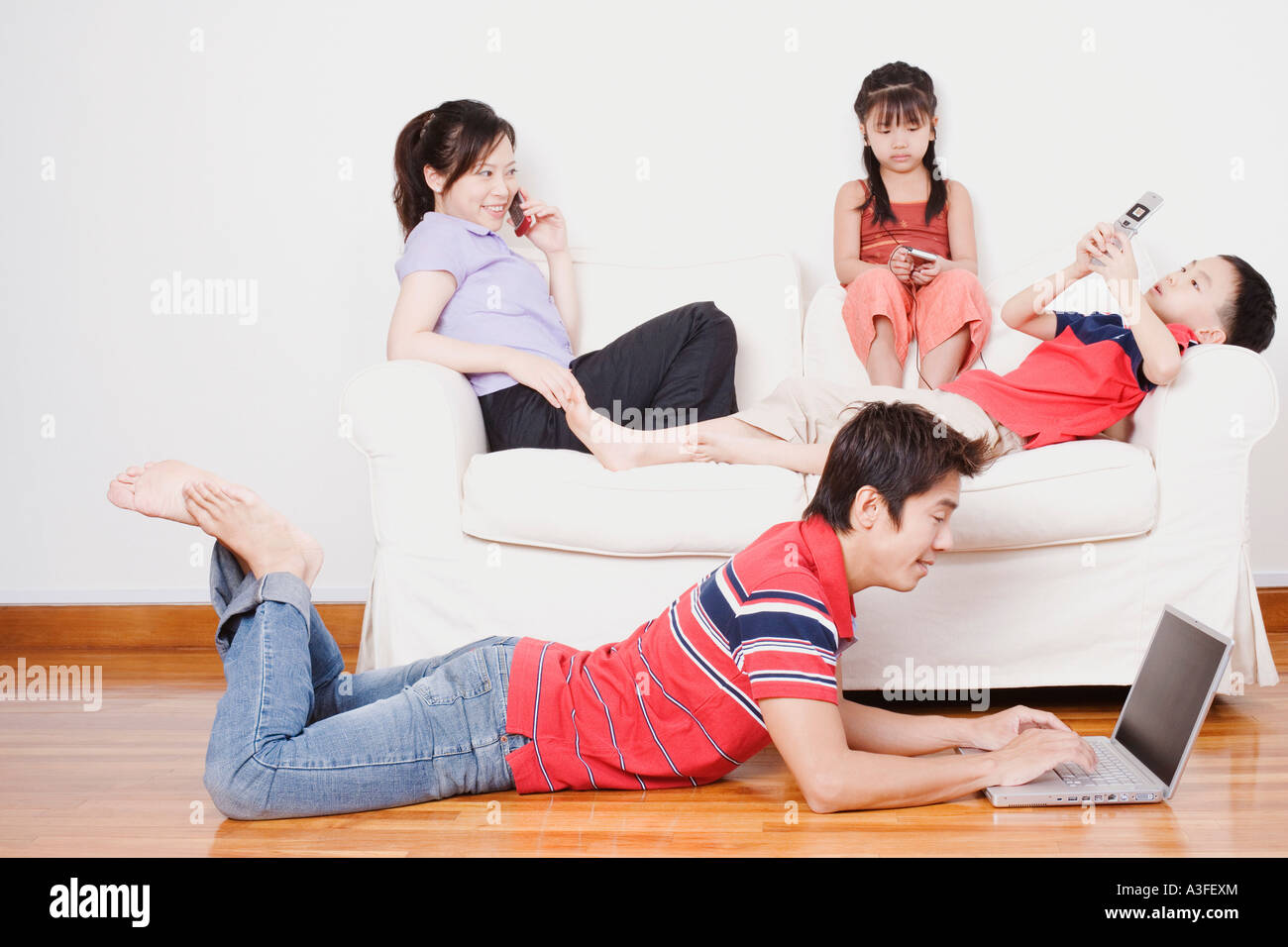 Young woman and her son and daughter sitting on a couch with a mid adult man lying on the floor with a laptop Stock Photo