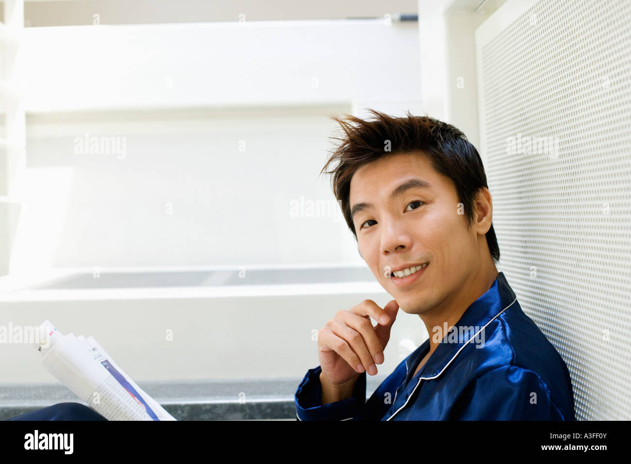 Portrait of a mid adult man holding a newspaper - Stock Image