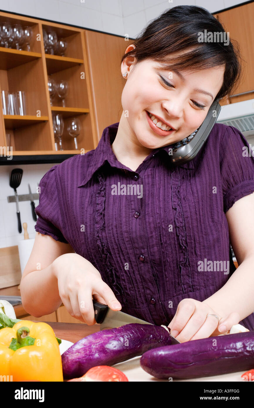 Close-up of a young woman cutting vegetables and talking on a cordless phone - Stock Image