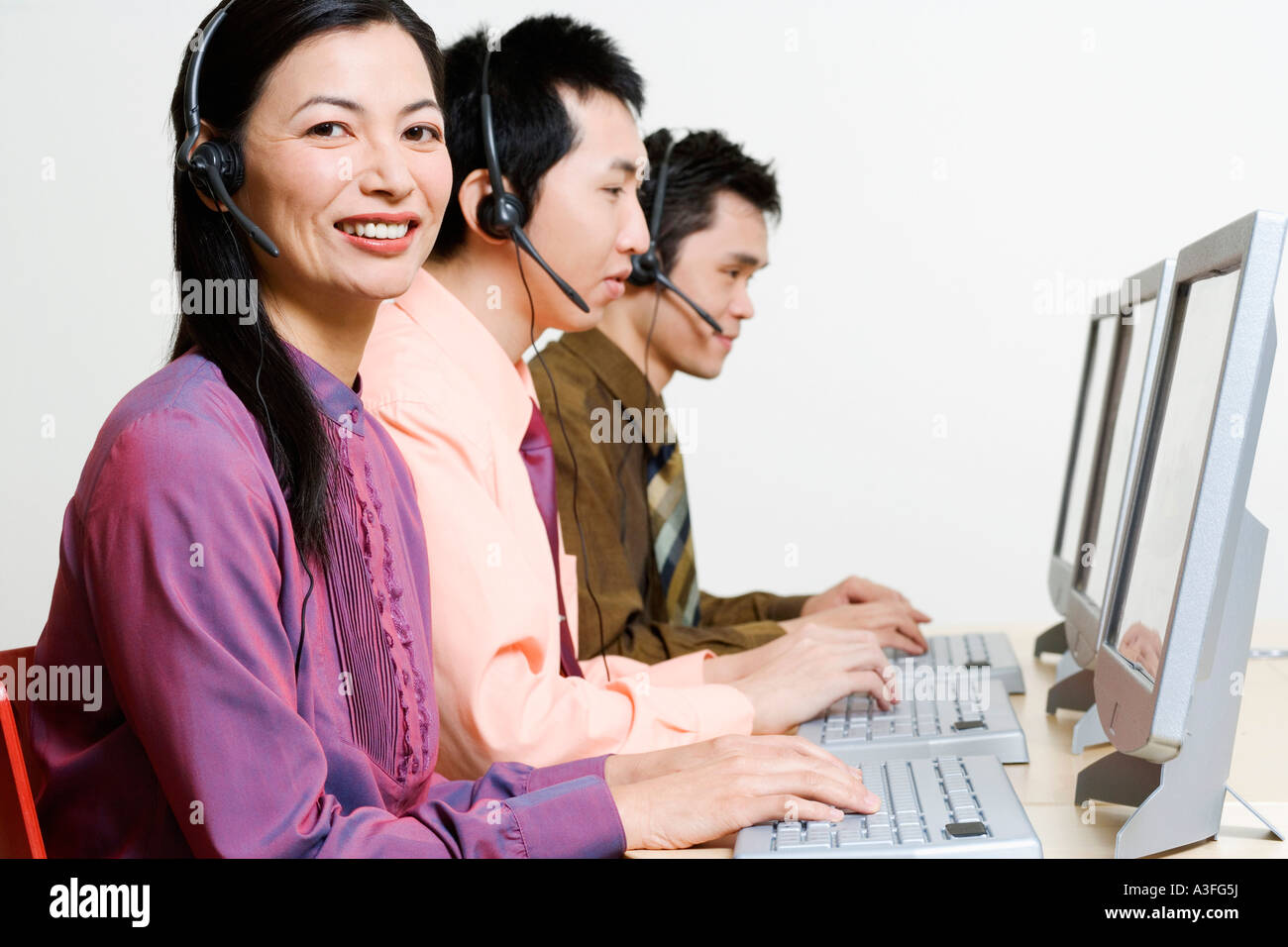 Three customer service representatives working on computers Stock