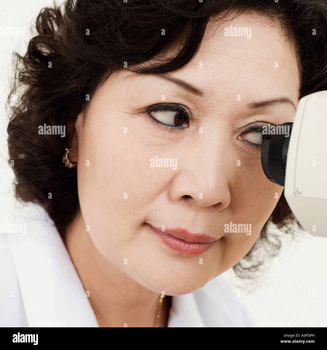 Close-up of an optometrist looking into an ophthalmoscope - Stock Image