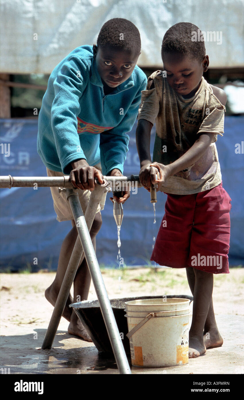Angola, boys fetching water at a dry water pipe in a refugee camp in Luau, border to Zambia - Stock Image