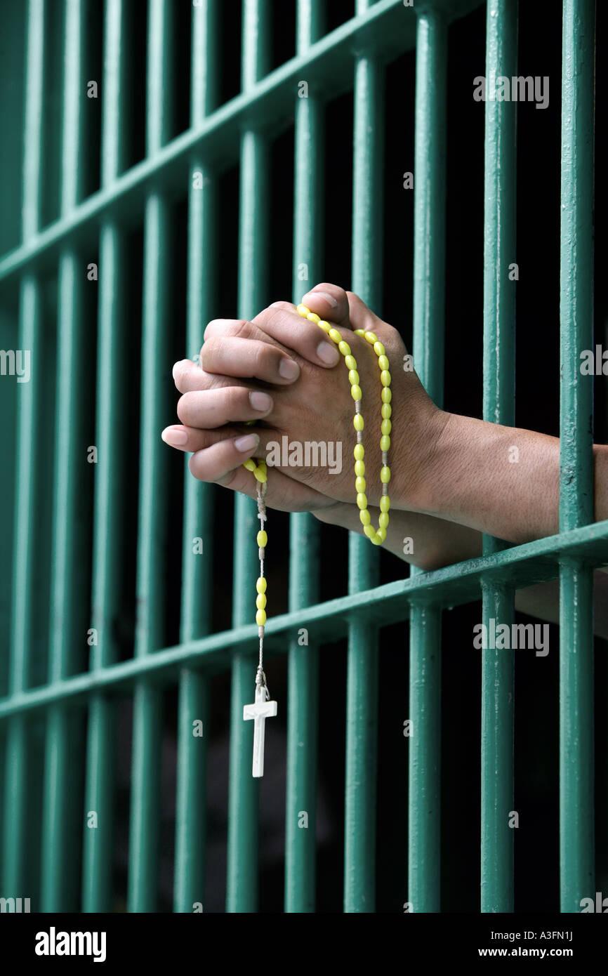 The Philippines, Prisoner behind bars praying the rosary Stock Photo