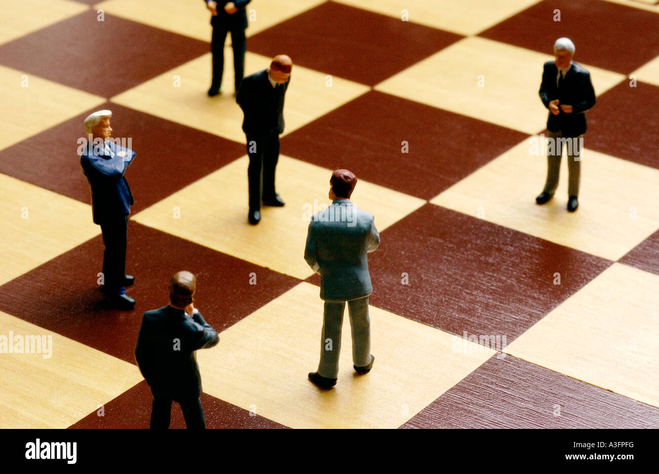 Businessmen figures on a chessboard - business competition / decision making / judgment / choices / strategy concept - Stock Image