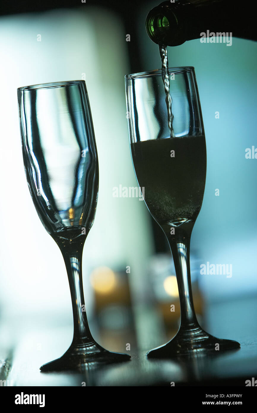 Two champaign glasses on a bar One is full and one is empty EQUIPMENT OBJECTS glass glasses household objects kitchen - Stock Image