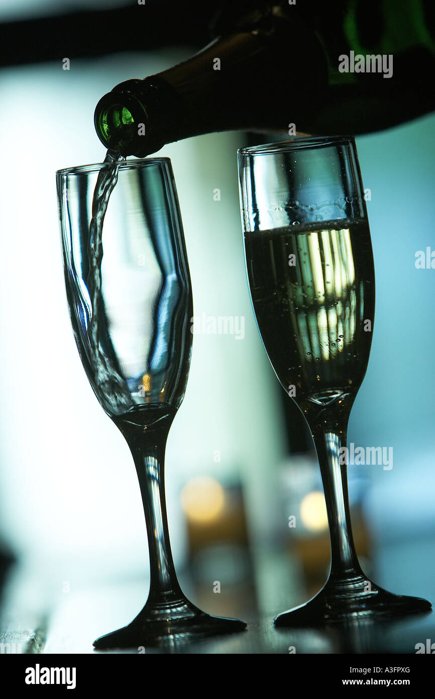 Two champaign glasses on a bar One is full and one is empty The empty one is about to be filled EQUIPMENT OBJECTS - Stock Image