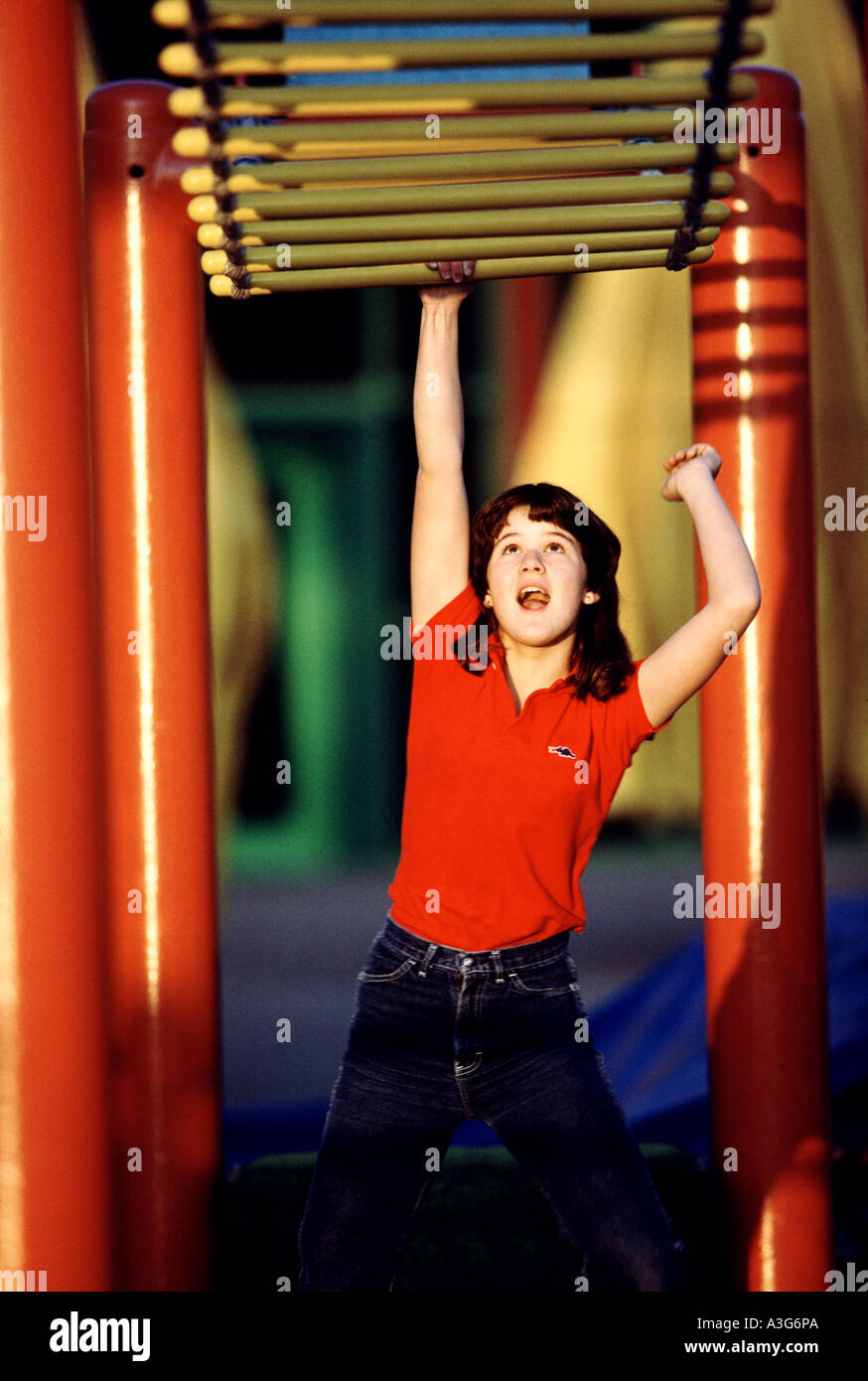 Cute young kid reaches and jumps up to grasp overhead monkey bars as the sun sets in a neighborhood park. - Stock Image