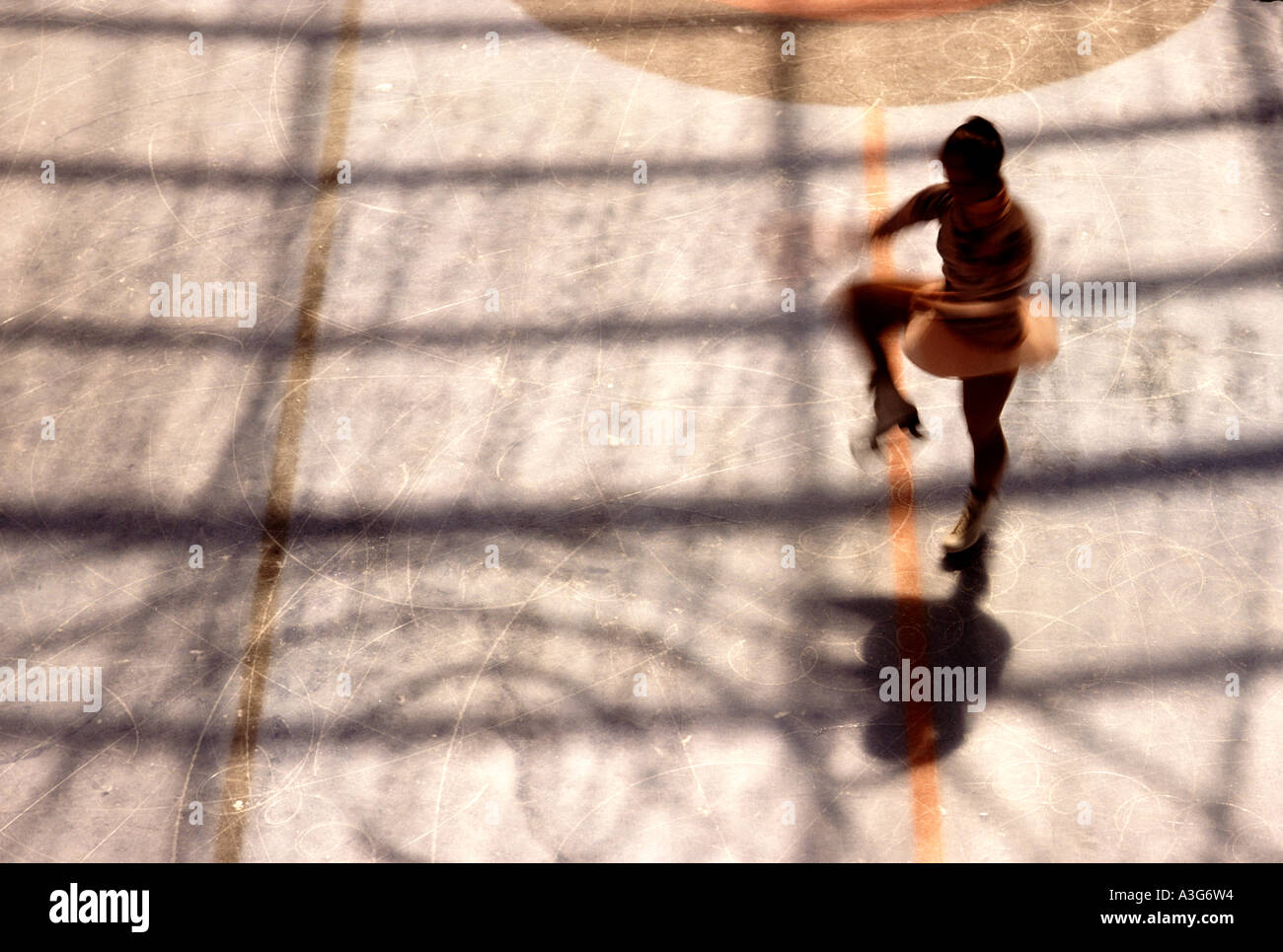 Dramatic overhead silhouette of a young woman practicing  for a figure skating competition in an in door ice rink. - Stock Image