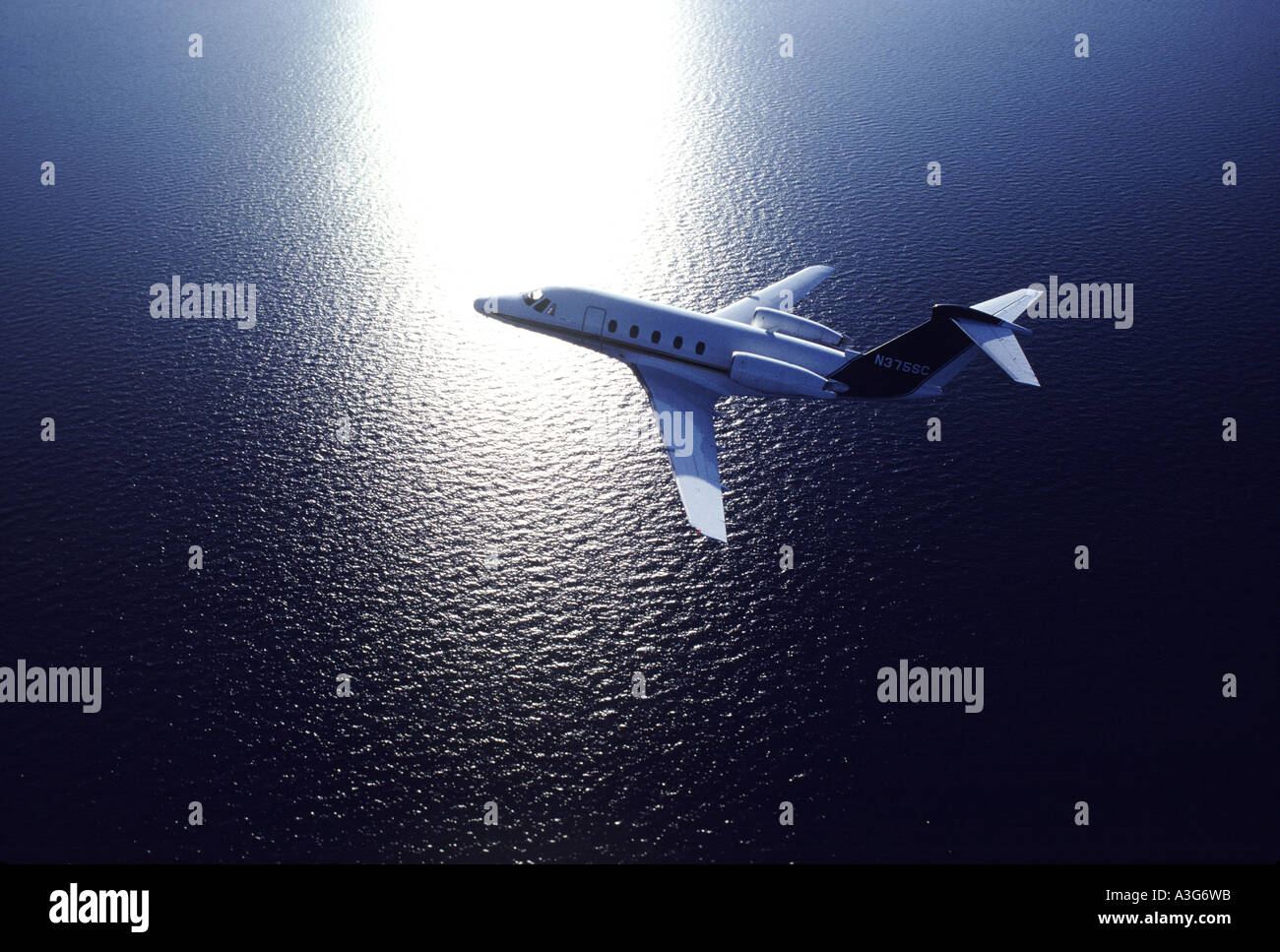 View of a luxuorious private aircraft flying over an expansive body of water as seen from above - Stock Image