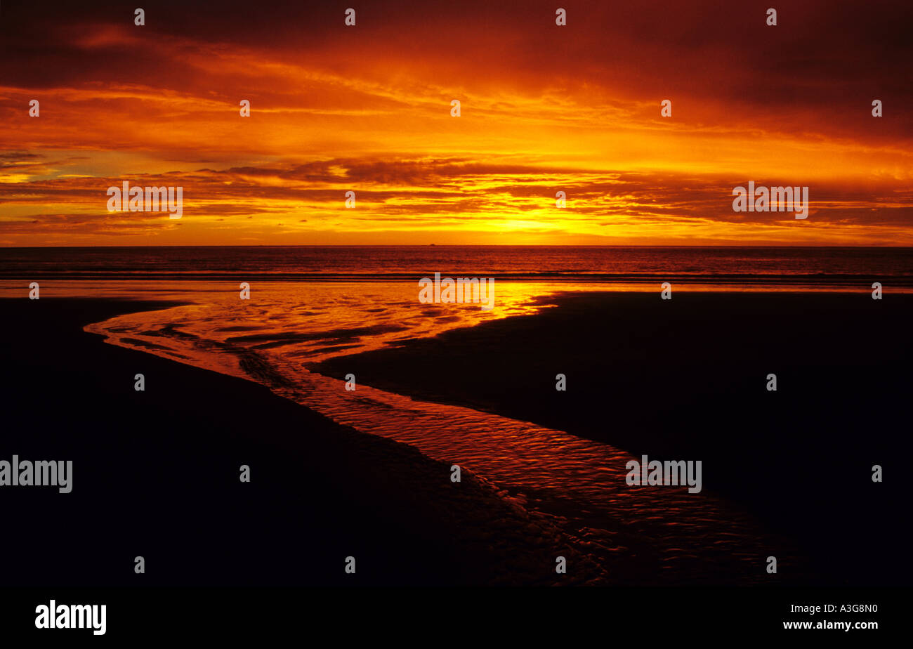 A stream flows over a beach into a red sunset at Rasa Ria Kota Kinabalu in Borneo - Stock Image