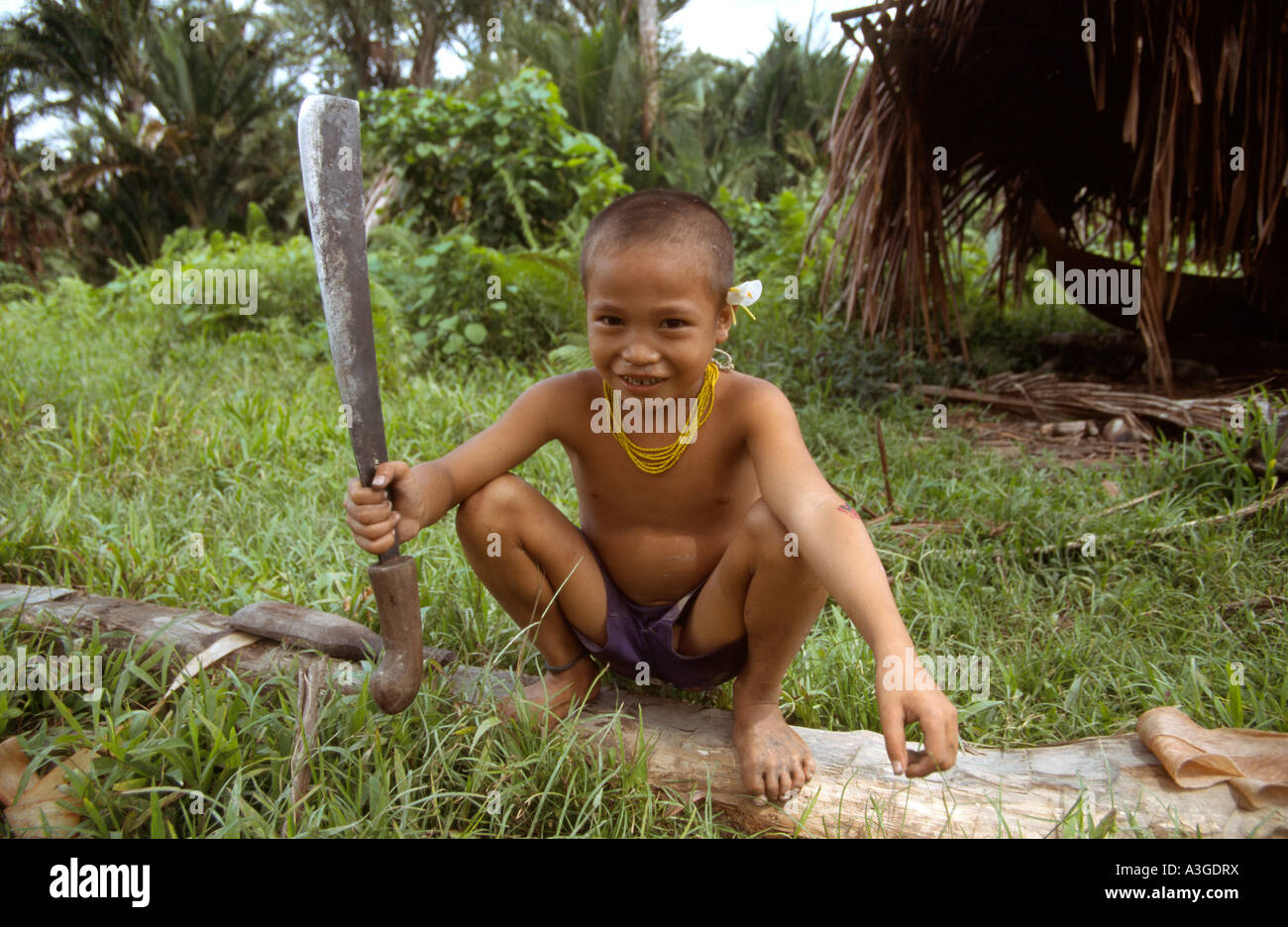 A Mentawai boy with a large machete in the Government Village. Siberut Island, Sumatra, Indonesia - Stock Image