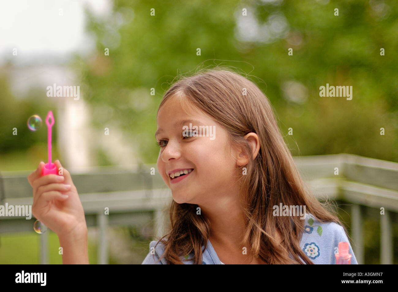 A little girl blowing bubbles Stock Photo