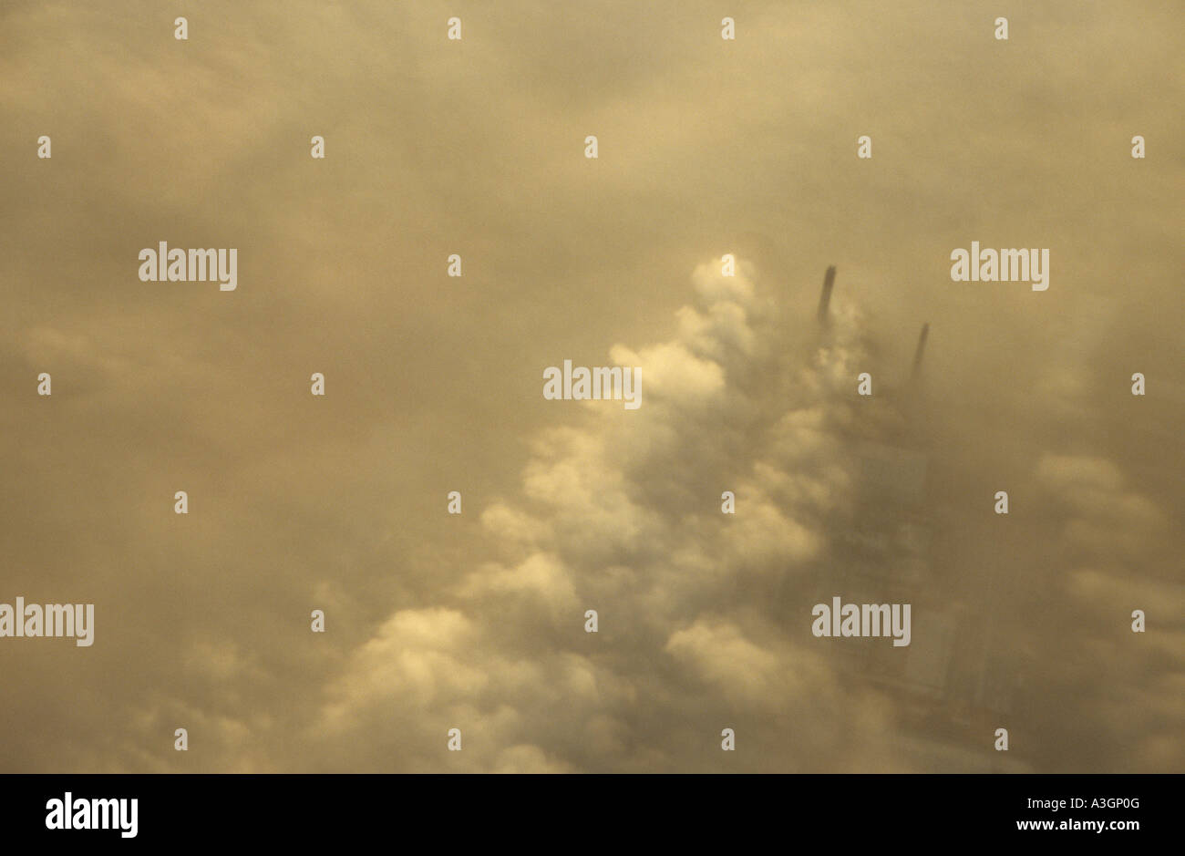 Aerial view of factory chimneys through the smog and fog of an English winter day near Heathrow London - Stock Image