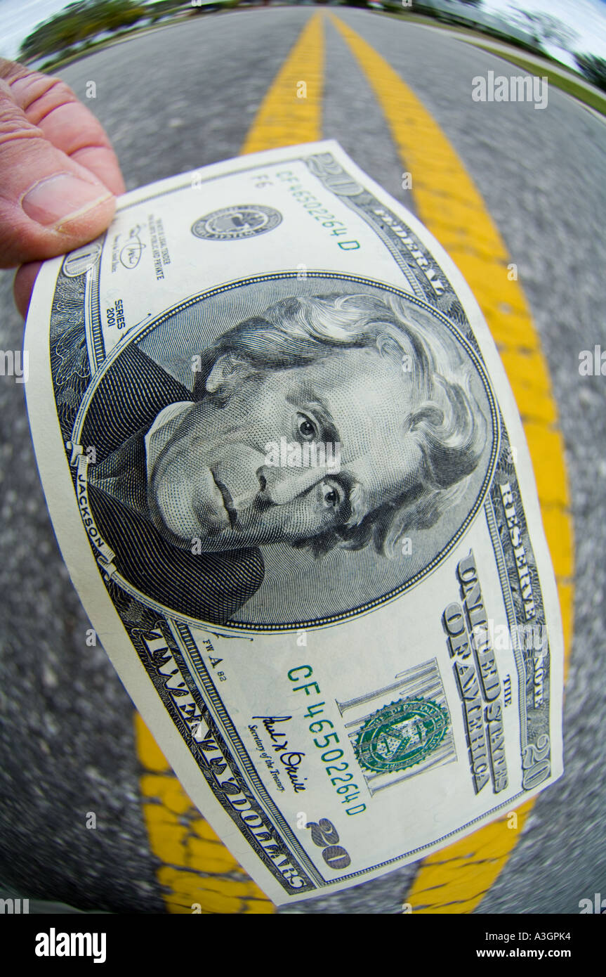 fish eye view of hand picking up a 20 dollar bill US on street - Stock Image