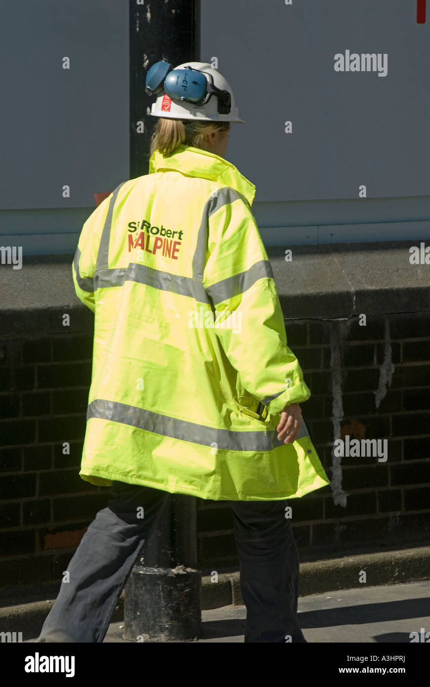 Woman construction industry site worker in Sir Robert McAlpine high visibility jacket & hard hat from major UK building Stock Photo