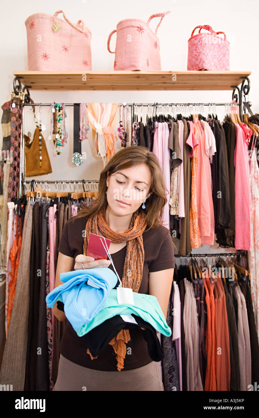 A woman looking at price tags - Stock Image