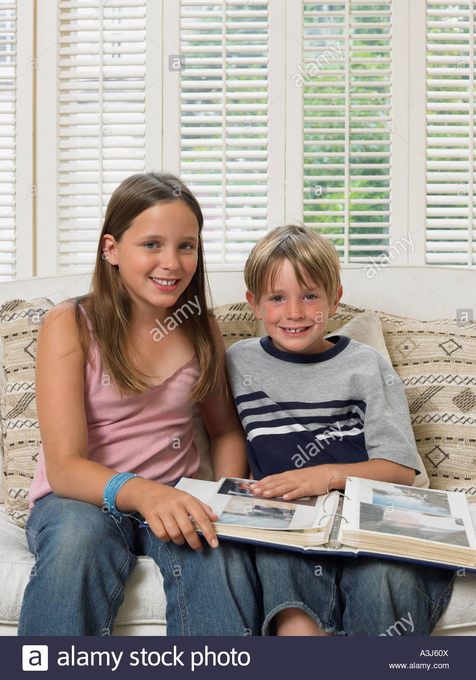 Brother and sister with photo album - Stock Image