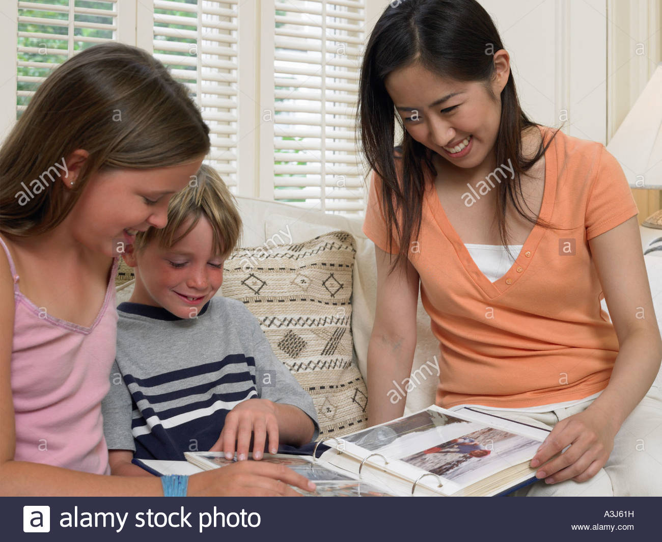 Children and exchange student looking at photo album - Stock Image