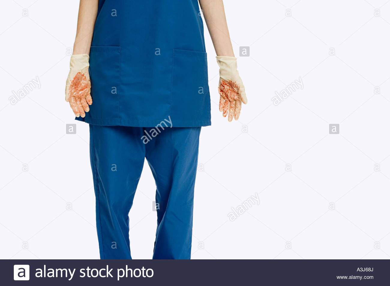 Surgeon wearing surgical gloves covered in blood - Stock Image
