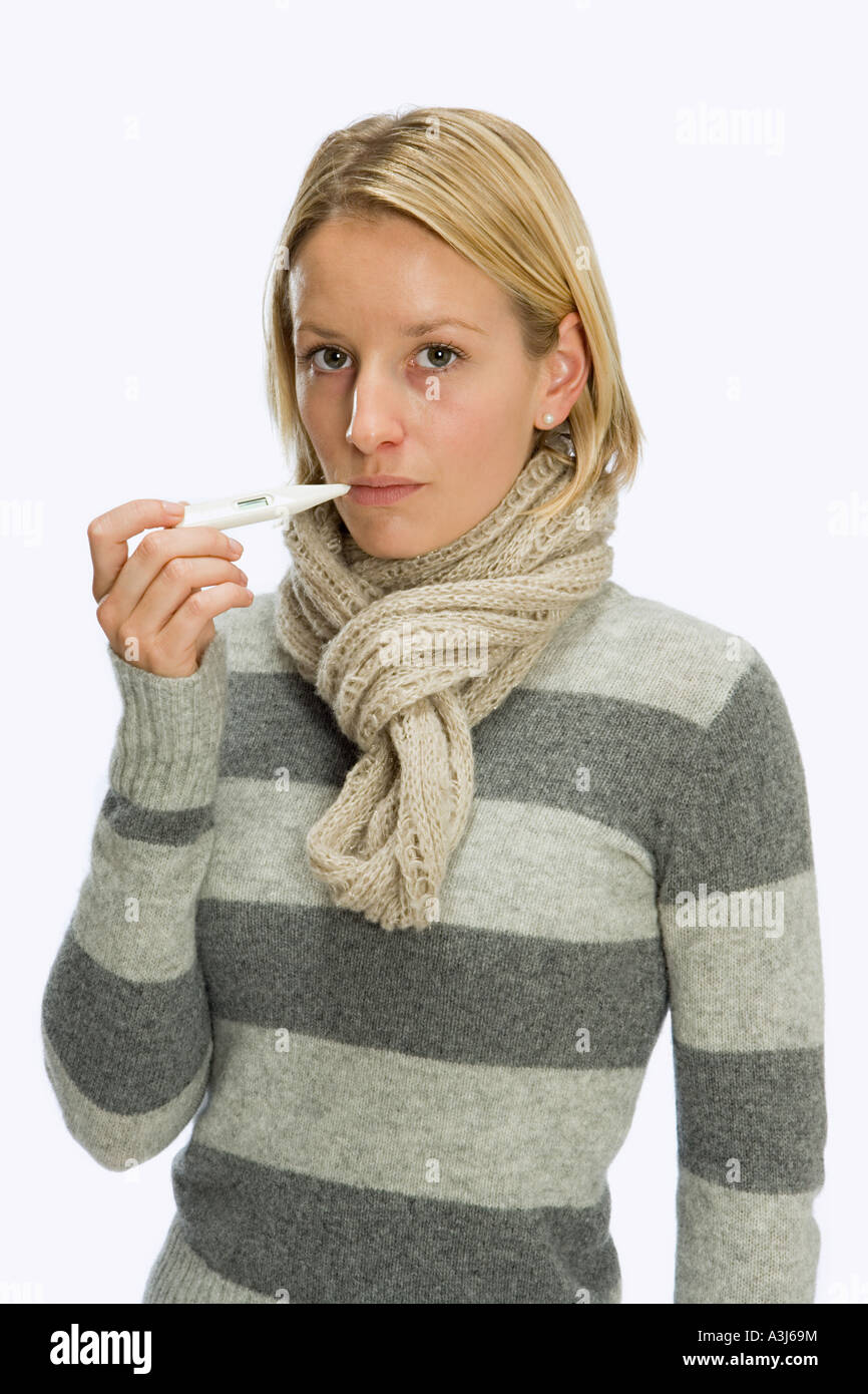 Woman using thermometer - Stock Image