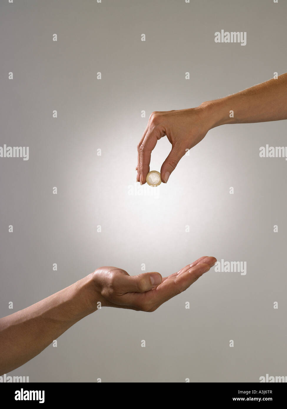 Woman holding coin above mans hand - Stock Image