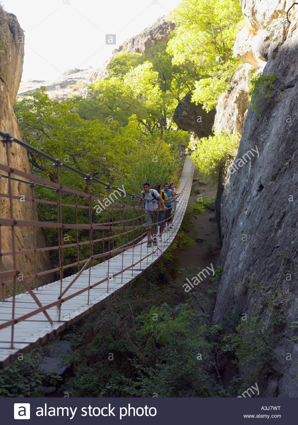 Teenagers walking across a bridge Stock Photo