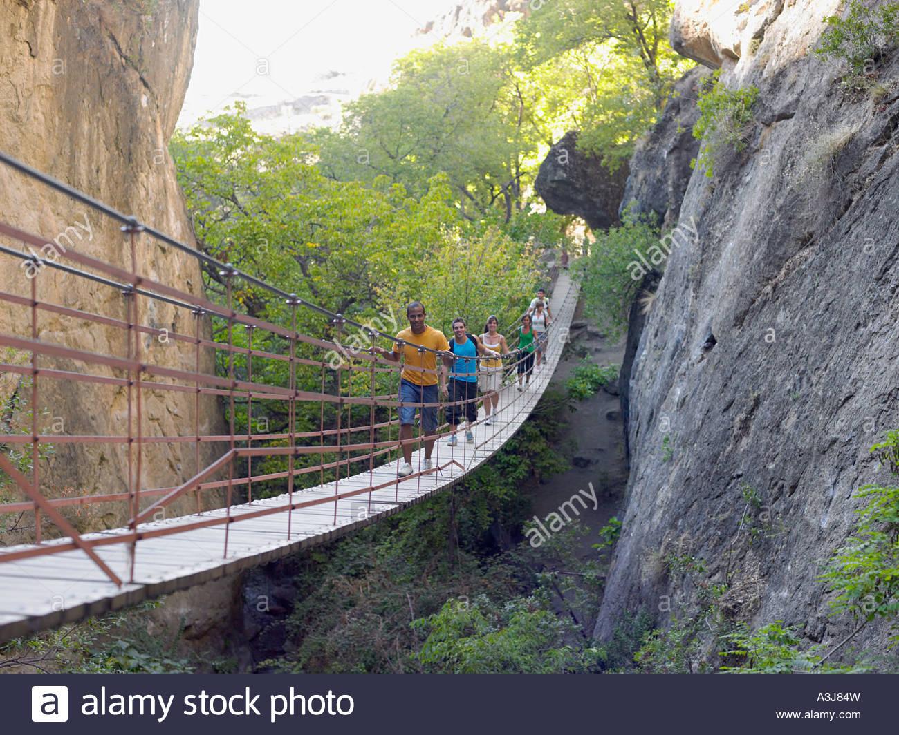 Group of teenagers walking across bridge Stock Photo