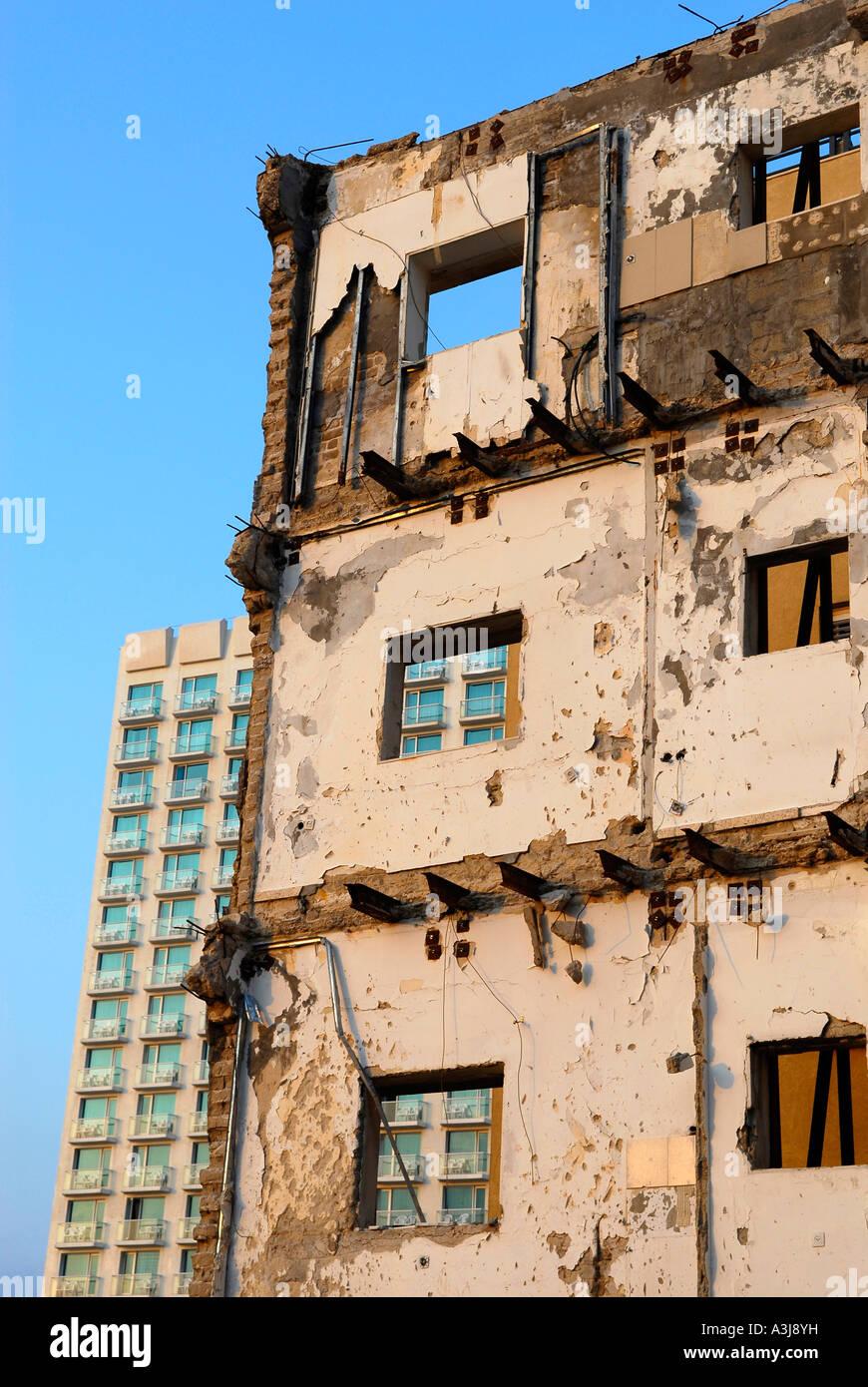Remnant of demolished building stands in stark contrast to modern hotel in Tel Aviv Israel - Stock Image