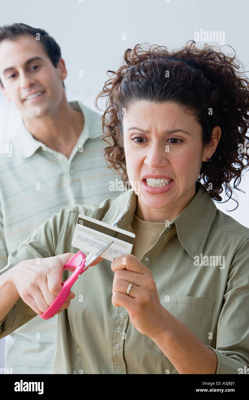 Couple cutting up a credit card - Stock Image