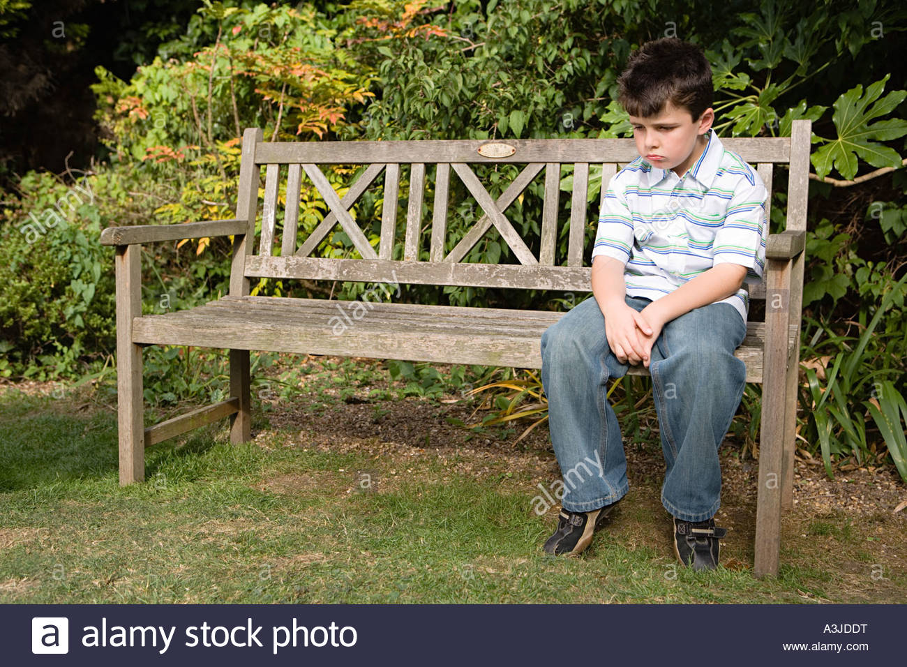 Sullen boy on a bench - Stock Image