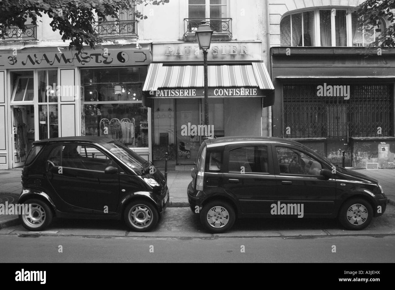 Two small cars parked on the streets of Paris. - Stock Image